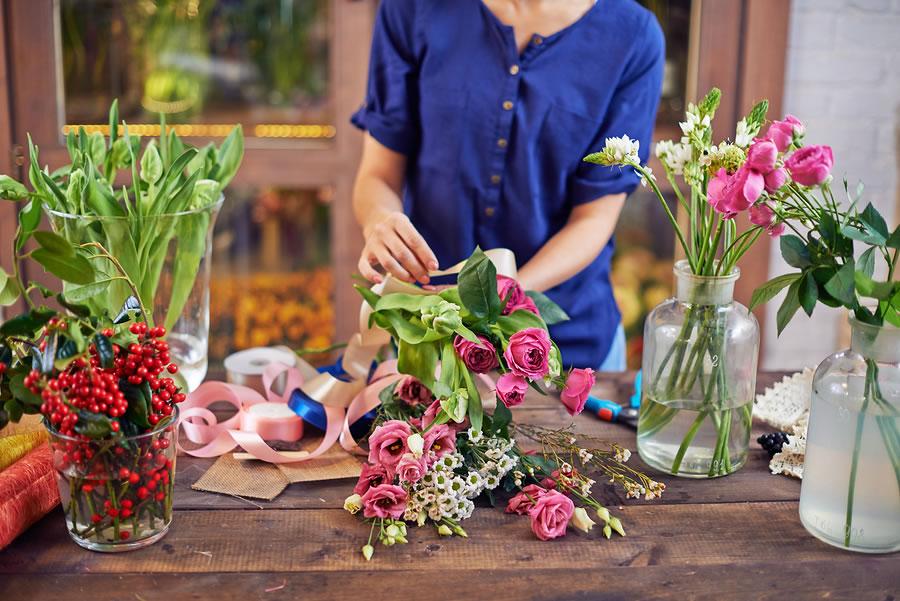 bigstock-Female-florist-tying-flowers-u-82215383